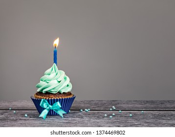 Blue Cupcake with bow, sprinkles and one candle over a gray background.