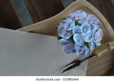 Blue cupcake design cream like blue Hydrangea flower Served on wooden tray with brown paper napkin and little fork, have some space for write wording