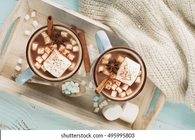 Blue Cups of hot Chocolate drink with Marshmallows and cinnamon on blue wooden background. Winter time. Holiday concept, Top view, toned