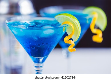 Blue curacao cocktail with lime, ice and mint in martini glasses on wooden background