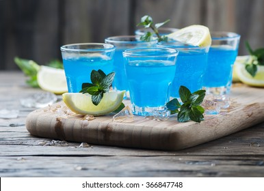 Blue curacao liqueur with lemon on the wooden table, selective focus