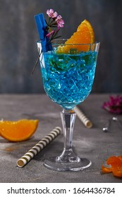 Blue curacao liquor with orange and flower for design on a gray background.