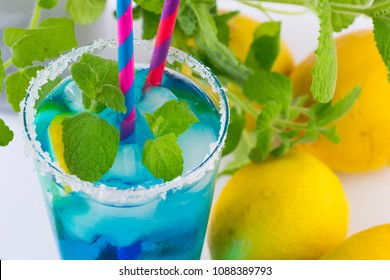 Blue Curacao refreshing drink with lime and lemon slices, garnished with fresh mint leaves.