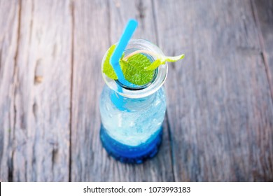 Blue Curacao soda Sparkling Mocktail with mint leaves. Refreshing drink, summer fragrance. beverage in a glass bottles put on a wooden table.