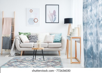 Blue curtain, posters and carpet in living room with blankets on ladder next to sofa with pillows