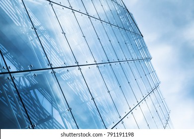 Blue curtain wall made of toned glass and steel constructions under cloudy sky