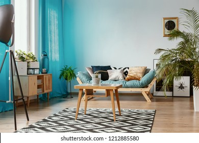 Blue curtains and wooden furniture in beautiful eclectic interior with comfortable sofa with pillows and coffee table, real photo with copy space