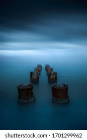 blue dark atmosphere around old woods pillars
