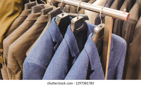 Blue and dark colored blazers hanging inside a shop.