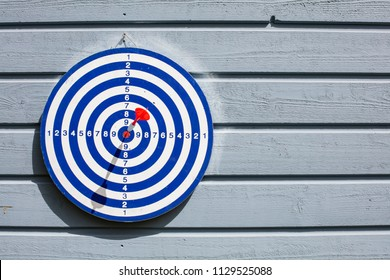 Blue dartboard and red dart. Dart is in the middle of the table, the bull's eye.