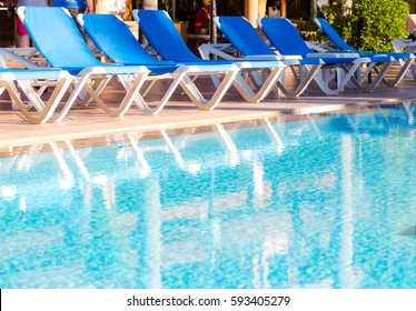 Blue deck chairs arranged around the pool before or after the end of the holiday season. Horizontal close up full frame composition