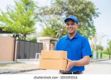 Blue Delivery man holding parcel cardboard box.