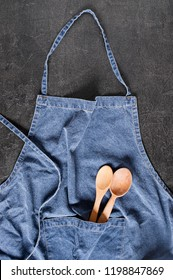 Blue denim apron with wooden spoons in the pocket on the dark gray textured table, flat lay
