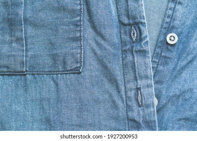 Blue denim clothing with buttons, top view background
