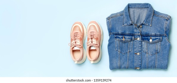 Blue denim jacket and trendy pink sneakers on blue background top view flat lay copy space. Denim, fashionable jacket women's or men's trend clothing, fashion beauty background. Spring Fashion Concept