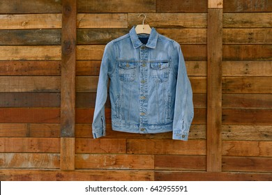 blue denim jean jacket hanging on wooden background