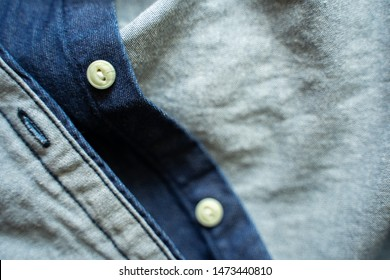 Blue denim shirt with white buttons close-up. Garment background