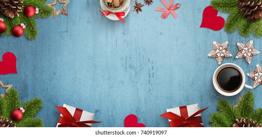 Blue desk with christmas decoration, gift, cup of coffee and gingerbread cookies. Empty space for text input