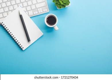 Blue desk office with laptop, smartphone and other work supplies with cup of coffee. Top view with copy space for input the text. Designer workspace on desk table essential elements on flat lay