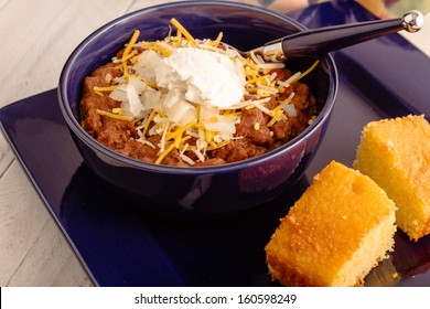 Blue dinner plate with bowl of elk meat chili with onions, sour cream and shredded cheese