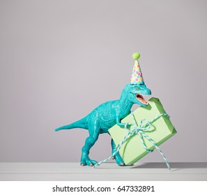 Blue dinosaur toy with birthday hat holding gift on a light grey background.