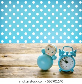 Blue doll roly poly and old alarm clock on a wooden table, retro style.