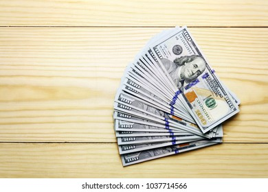 A lot of blue dollars heap on wood background
