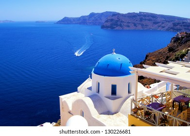 Blue dome church with boat, Oia village, Greece