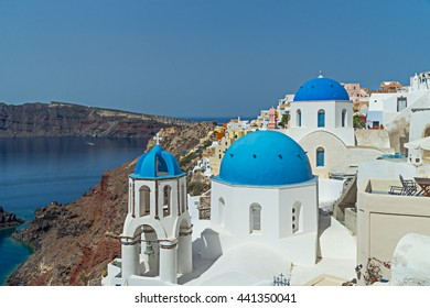 Blue domed church in Oia village on top of the cliffs on Santorini in the Greek Islands