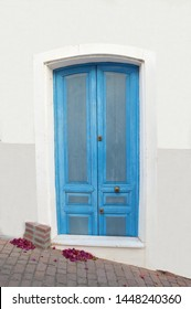 Blue Door with Bugambilia flower petals on the cobblestone sidewalk in Mojacar, Almeria a more than 2000 year old town with only whitewash buildings in the Andalusian region of Spain Europe
