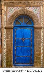 Blue door in Essaouira Medina with ornate stonework and Zellige tilework
