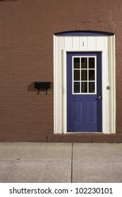 blue door on red brick wall at night