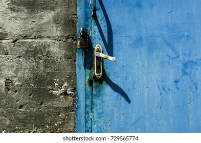 Blue door with padlock and gray wall