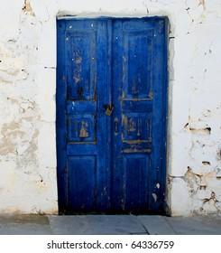 blue door set in a rock wall