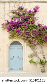 blue door with a stone wall and a wall-growing tree with purple blossoms in Mdina, Malta. Ancient architecture of the Mdina - the ancient capital of Malta