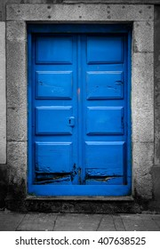 A blue door at the tourist street in Porto, Portugal. The surrounding walls and the porch are desaturated.