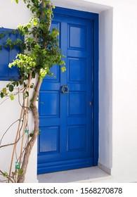 Blue door of white Greek house in Mykonos . Cyclades, Greece
