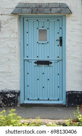 A blue door in a white wall in a house in Polperro in Cornwall
