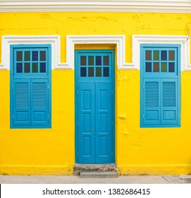 Blue door and windows on yellow wall, property and real estate concept