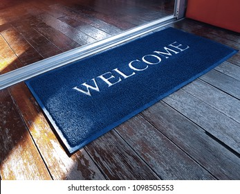 Blue Doormat with Welcome Text in Front of Shop