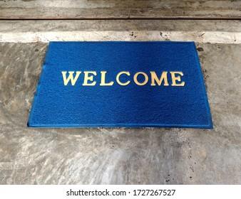 blue doormat with word welcome on cement floor in front of door step