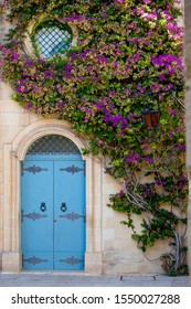 Blue doors framed by violet flowers