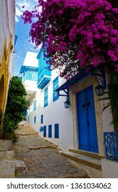 Blue doors, window and white wall of building in narrow street with moped in Sidi Bou Said, Tunisia. White-blue city of Sidi Bou Said, Tunisia. Eastern fairy tale with a French charm.