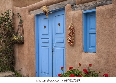 /Blue doors/Blue doors of an old adobe house in Taos, New Mexico. Hanging peppers and indian corn.