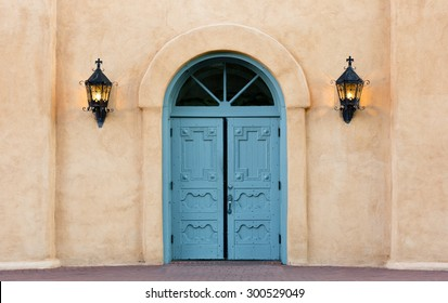 Blue, double doors of San Felipe de Neri church in Old Town, Albuquerque, New Mexico.  Iron lanterns on adobe wall.  Building listed on National Register of Historic Places.