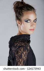blue dramatic eyeshadow eye make-up trend with hair in the messy top knot on a beautiful young woman wearing a lace blouse