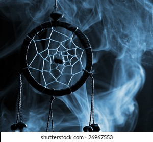 blue dream catcher in smoke isolated on black