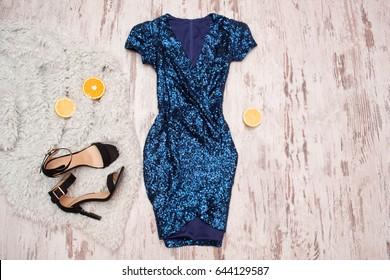 Blue dress in sequins, black shoes and halves of orange. Wooden background, fashionable concept