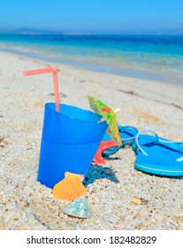 blue drink with sandals on a tropical shore