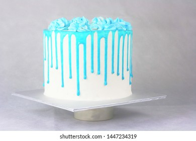 Blue dripping cream cake with grey background